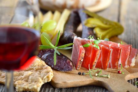 Jihotyrolská vydatná svačinka se slaninou, sýrem, pikantní horské vyléčených párků a sklenicí místního červeného vína Reklamní fotografie - 45153144