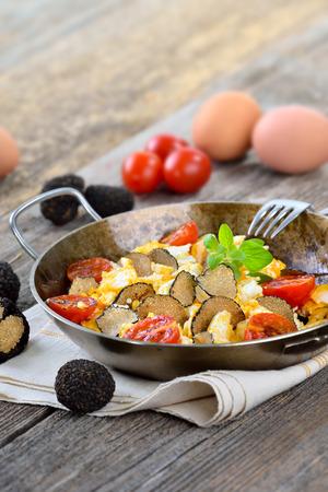 huevos revueltos: huevos revueltos con trufas negras frescas procedentes de Francia servidos en una sartén Foto de archivo