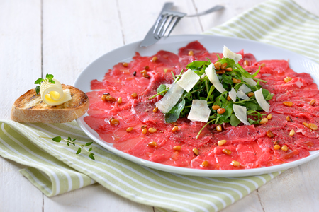 downloaded: Carpaccio of beef fillet with rocket salad, parmesan cheese and roasted pine nuts, served with a slice of toasted baguette with a butter roll Stock Photo