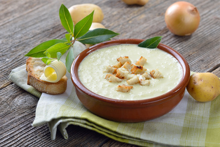 Homemade cream of potato soup with croutons, served with toasted ciabatta bread with a butter roll Standard-Bild