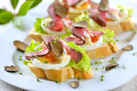 truffe blanche: Canapes with roast beef, black truffles autumn, French brie cheese on a slice of egg on baguette with a leaf of salad Banque d'images