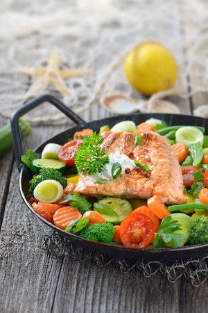 Tasty fried and grilled salmon fillet on mixed vegetables served in a colorful frying pan, lemons and a fishing net in the background Stock Photo