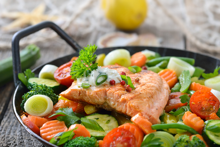 Tasty fried and grilled salmon fillet on mixed vegetables served in a colorful frying pan, lemons and a fishing net in the background Reklamní fotografie
