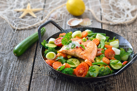 downloaded: Tasty fried and grilled salmon fillet on mixed vegetables served in a colorful frying pan, lemons and a fishing net in the background Stock Photo