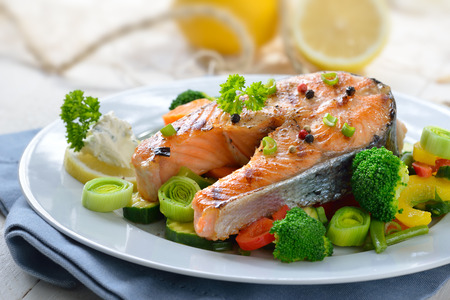 healthy meals: Tasty Grilled salmon steak on mixed colorful vegetables, lemons and a fishing net in the background Stock Photo