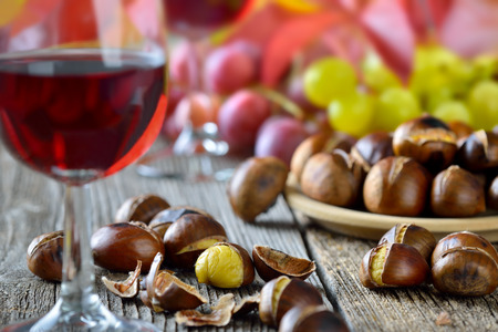 Roasted chestnuts with South Tyrolean red wine on an old wooden table Reklamní fotografie - 47223944