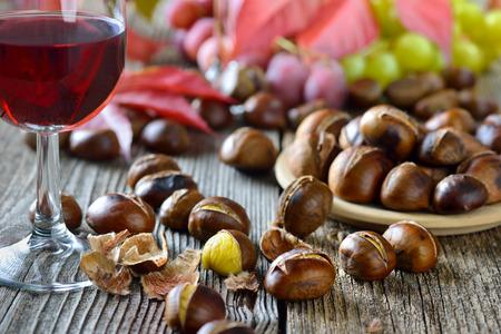 Castañas asadas con Tirol del Sur vino tinto en una vieja mesa de madera