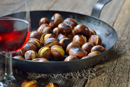 Roasted chestnuts served in a chestnut pan on an old wooden table with a glass of Italian red wine