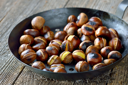 downloaded: Roasted chestnuts served in a special perforated chestnut pan on an old wooden table