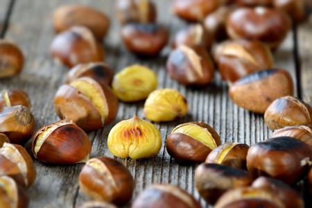 Roasted chestnuts - ready to eat - on a rustic wooden table