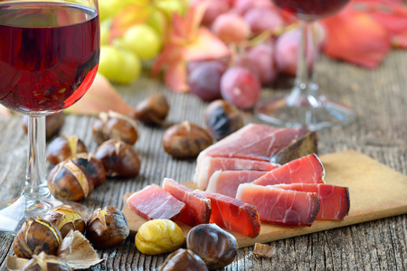 Roasted chestnuts with South Tyrolean bacon and a glass of red wine Stock Photo