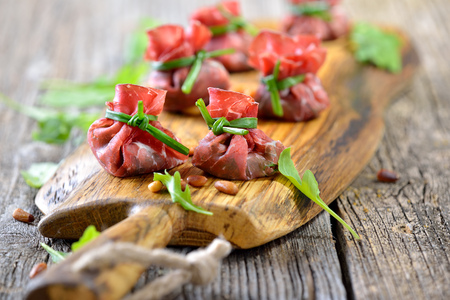 Italian bresaola beef ham stuffed with chopped rocked salad, roasted pine nuts, parmesan cheese and creamy balsamic vinegar, tied up with blanched chives