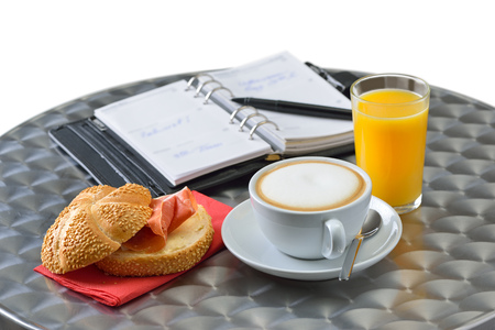 quick snack: Business snack with a ham sandwich, a cappuccino and a glass of orange juice; a personal organizer in the background