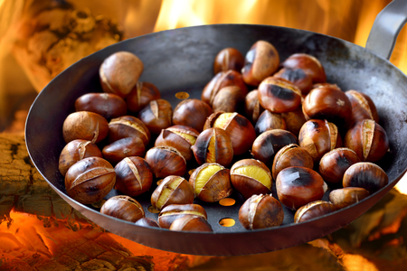 Roasting chestnuts in a special pan over an open fire