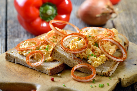 spread around: A Bavarian snack: So Called Obazda - cheese specialty made of melted camembert with cream cheese and butter, onions, a splash of beer and some spices - served on rustic bread with onion rings Stock Photo