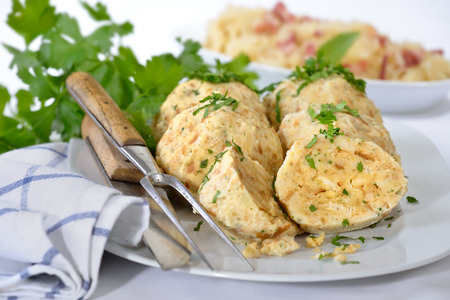 downloaded: Bavarian bread dumplings served on a white platter, garnished with parsley, sauerkraut with bacon in the background