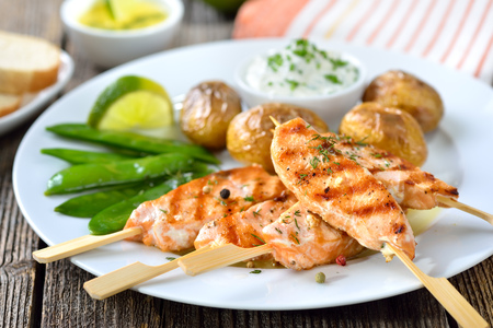 brochetas de frutas: Grilled salmon skewers served with snow peas and baked potatoes with sour cream