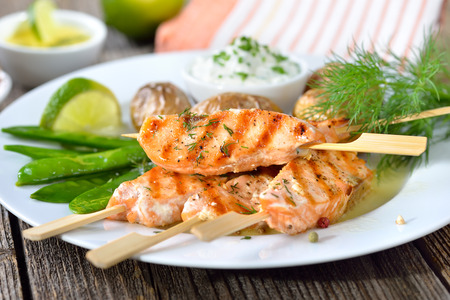 Sour cream: Grilled salmon skewers served with snow peas and baked potatoes with sour cream