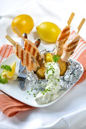 Délicieux pomme de terre cuite avec la crème sure et brochettes de saumon grillées Banque d'images