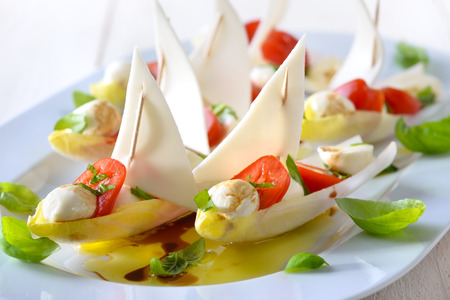 Chicory sailboats: Chicory leaves stuffed with cherry tomatoes and mozzarella balls, dressed with olive oil and balsamic vinegar