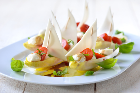 chicory: Chicory sailboats: Chicory leaves stuffed with cherry tomatoes and mozzarella balls, dressed with olive oil and balsamic vinegar Stock Photo