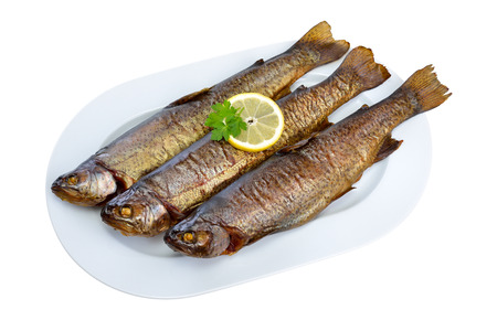salmo trutta: Three smoked rainbow trouts on a white plate isolated on white background Stock Photo