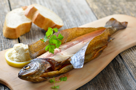 salmo trutta: Smoked rainbow trout served on a wooden cutting board with horseradish, parsley, lemon and baguette