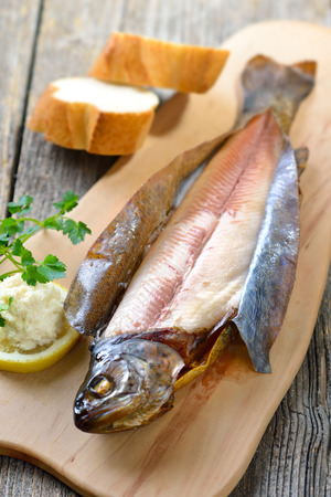 salmo trutta: A smoked rainbow trout served on a wooden cutting board with horseradish, parsley, lemon and baguette