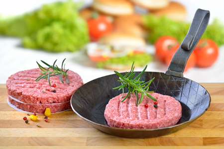 food preparation: Raw burger patty in on iron frying pan ready to fry, some burger ingredients in the background