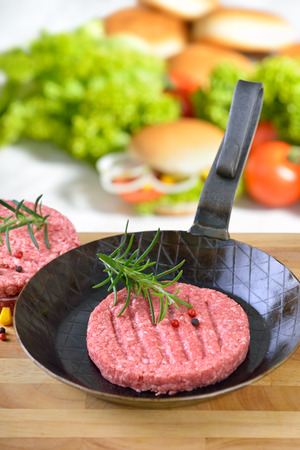 fresh food: Raw burger patty in on iron frying pan ready to fry, some burger ingredients in the background