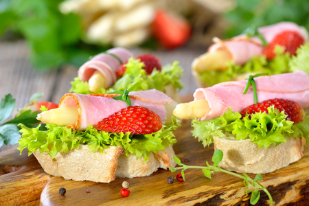 dainty: Dainty morsels with ham rolls and white asparagus with fresh strawberries on crispy baguette with leaves of lollo bionda