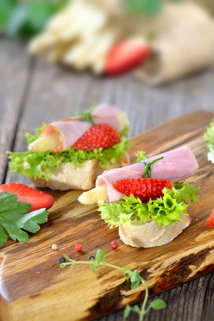 morsels: Dainty morsels with ham rolls and white asparagus with fresh strawberries on crispy baguette with leaves of lollo bionda