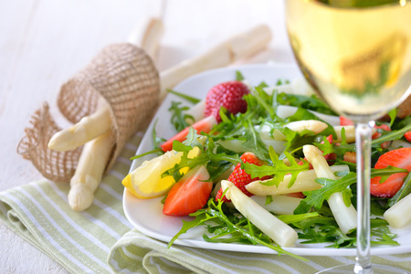 Colorful spring salad with fresh white asparagus, rocketsalad and strawberries, served with a glass of dry and fruity white wine