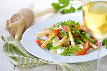 Mixed salad with fried white asparagus, Greek feta cheese, rocket and cherry tomatoes, served with a glass of dry white wine