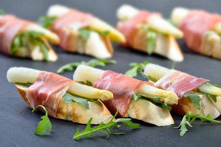 appetizers: Dainty morsels with white asparagus on rocket leaves wrapped with Italian prosciutto