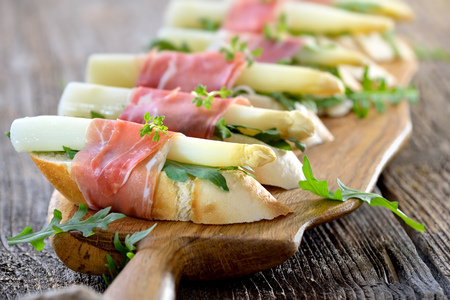 dish: Dainty morsels with white asparagus on rocket leaves wrapped with Italian prosciutto