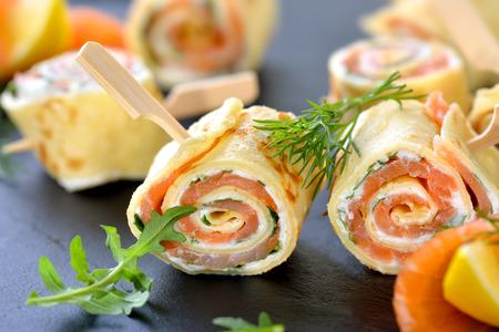 Rolki cienkie naleśniki z wędzonym łososiem, serem i śmietaną chrzanową rukolą