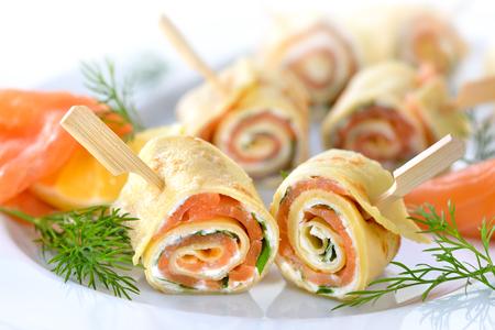 Rollos de crepes finas con salmón ahumado, queso crema de rábano y hojas de rúcula Foto de archivo