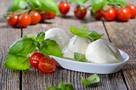 Three mozzarella cheese balls in a white bowl, garnished with cherry tomatoes and basil
