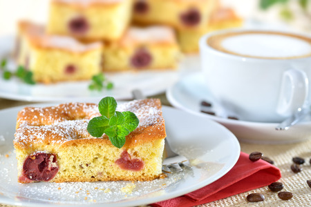 fruitcake: Delicious piece of cherry cake with a fresh cup of cappuccino