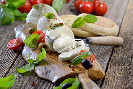 Italian mozzarella cheese snack with cherry tomatoes, basil and olives served on a wooden board with toast bread Фото со стока