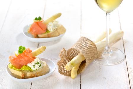 salmon ahumado: canapés deliciosos con espárragos blancos alemán, queso crema con hierbas, salmón ahumado en pan de chapata italiana con hojas de lechuga, servido con una copa de vino blanco