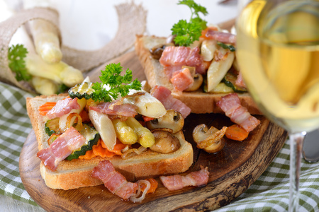 downloaded: Toast with fried white asparagus, other vegetables and bacon on a wooden board, served with a glass of white wine Stock Photo