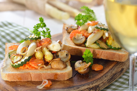 grilled vegetables: Vegetarian toast with fried white asparagus and other vegetables on a wooden board, served with a glass of white wine
