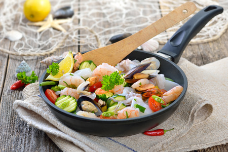 combining: Mixed seafood and fresh vegetables in a pan before cooking, food combining Stock Photo