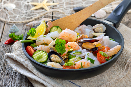 cooked: Mixed seafood and fresh vegetables in a pan before cooking, food combining Stock Photo