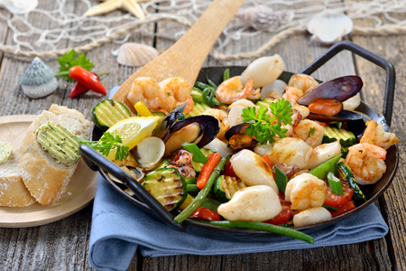 combining: Fried mixed seafood and fresh colorful vegetables served in a iron frying pan with slices of baguette with herb butter