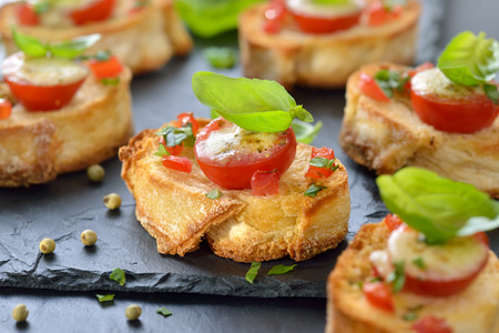 party tray: Delicious hot starters: Crispy baked crostini with tomato, mozzarella, olive oil and basil, served on a slate