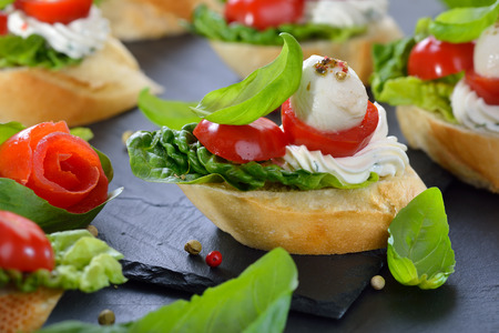 tomato slices: Delicious cold starters: Slices of baguette with cherry tomato, mozzarella, cream cheese, olive oil and basil leaves Stock Photo