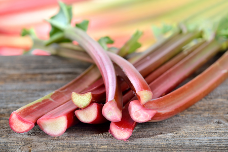 Fresh rhubarb on a wooden table in the background other rhubarb stalks in soft focus